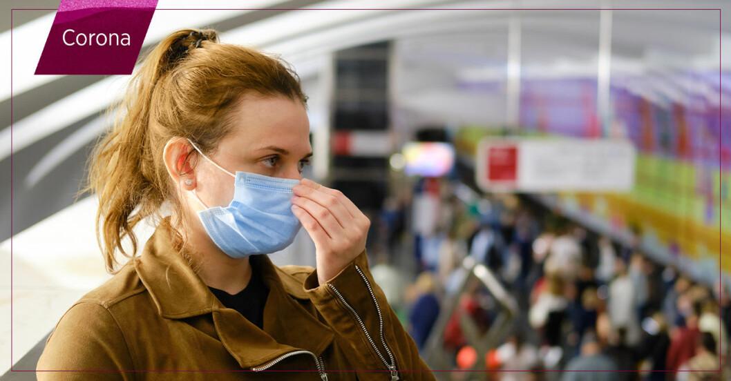 Kvinna i munskydd på tågstation med många människor