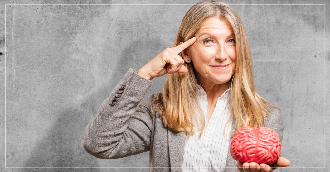 Äldre kvinna som håller i en konstgjord hjärna och pekar på sitt huvud.