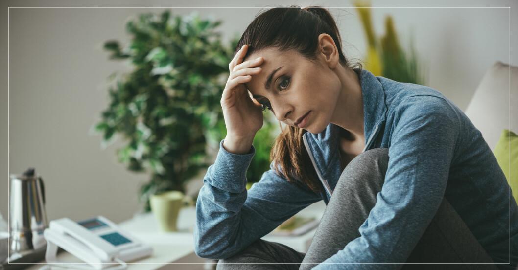 Bekymrad och förvirrad kvinna sitter och funderar