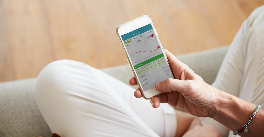 Kvinna sitter och tittar i en hälsoapp i sin mobil