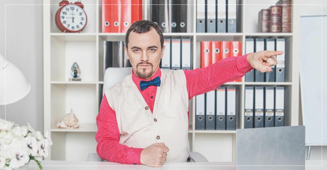 Arg man sitter i kontorsmiljö och pekar med ena handen bort mot något.