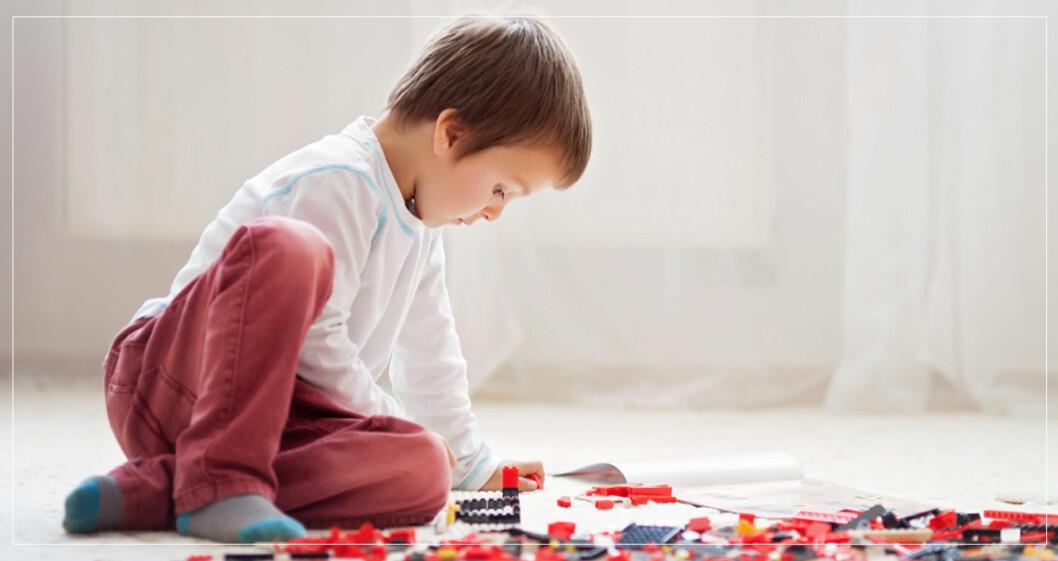 Pojke som leker med lego på golvet.