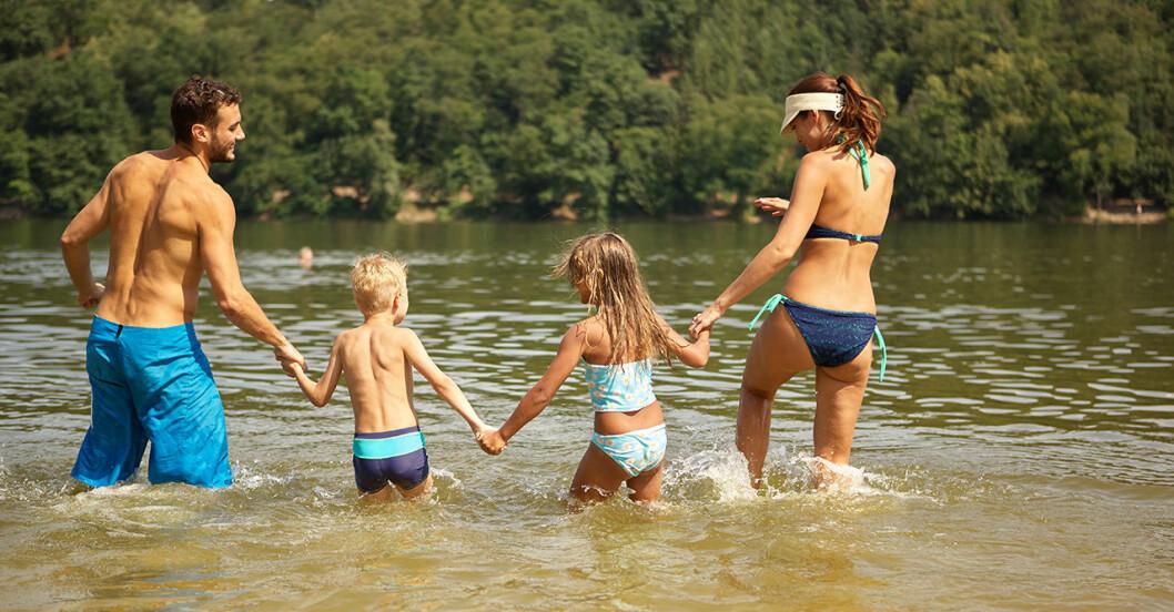 Familj som går hand i hand ner i vattnet
