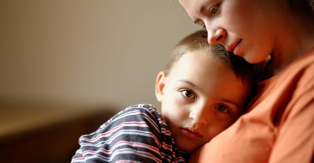 Litet barn kramar om sin mamma med oro i blicken