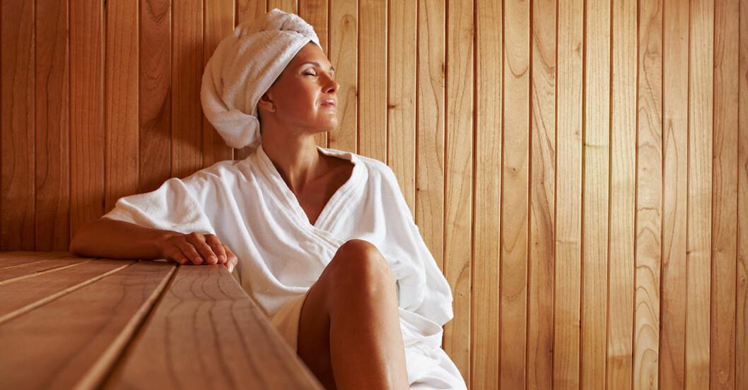 Kvinna i vit badrock njuter i en bastu