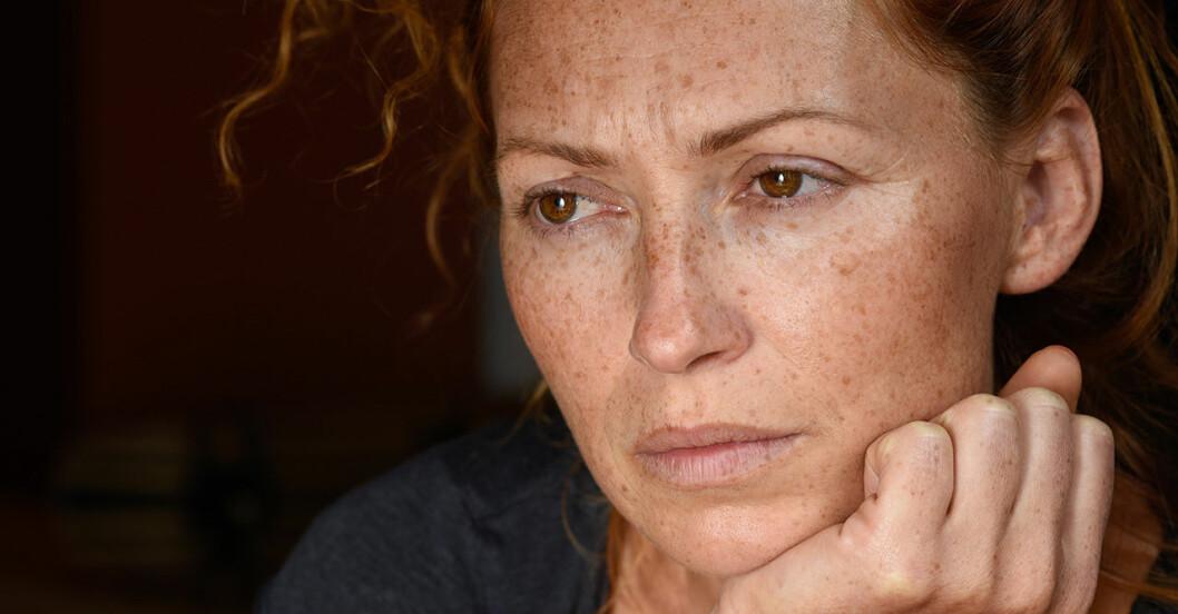 Fräknig kvinna som ser bekymrad ut