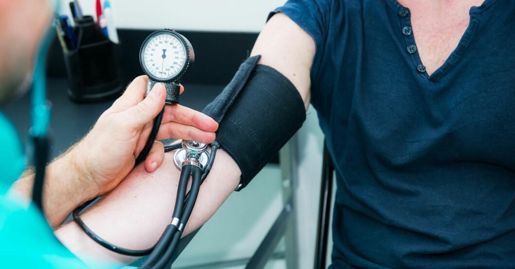 Doktor mäter blodtrycket på en kvinnas överarm