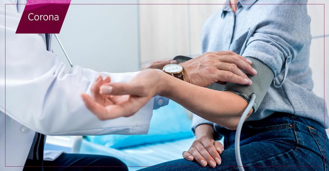 kvinna får blodtryck mätt av doktor