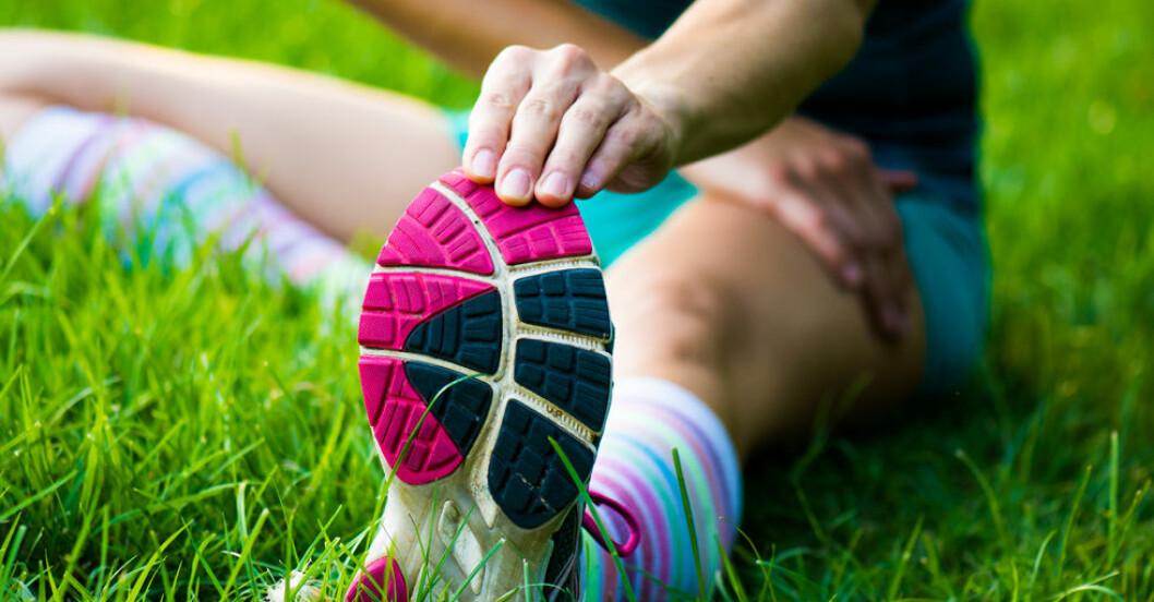 kvinna stretchar foten