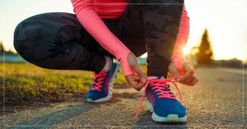 Kvinna knyter skorna på löprundan.