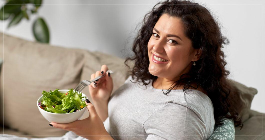 Kurvig kvinna äter sallad i soffa.