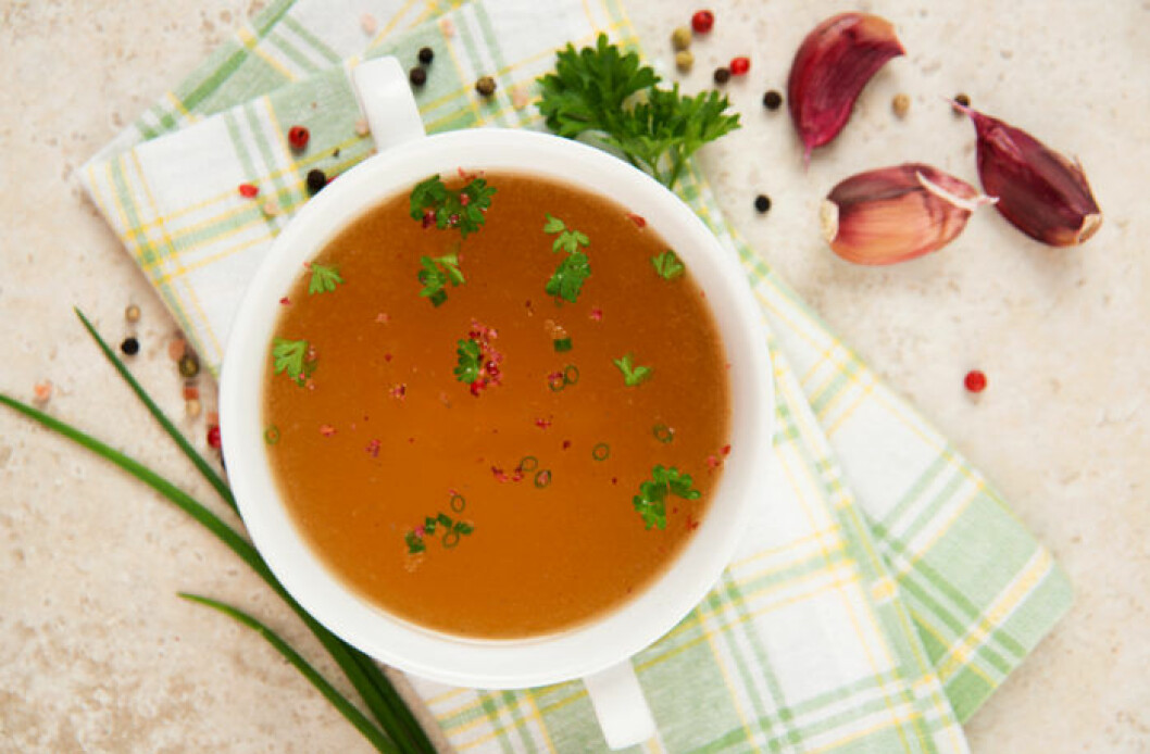 En skål med buljong på en kökshandduk. Bredvid ligger ett par vitlöksklyftor, persilja och gräslök.