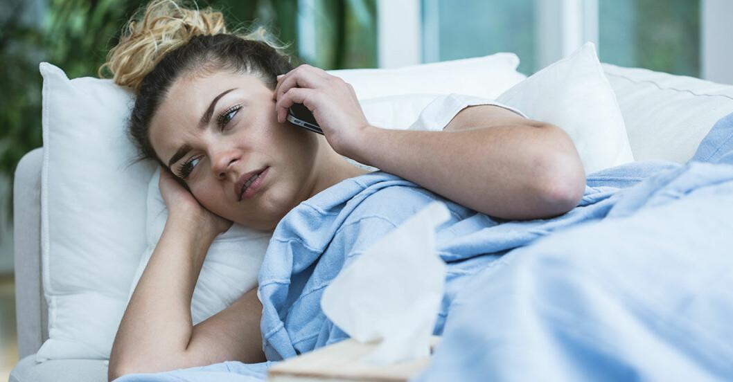 Förkyld kvinna ligger nedbäddad i sängen och rínger doktorn