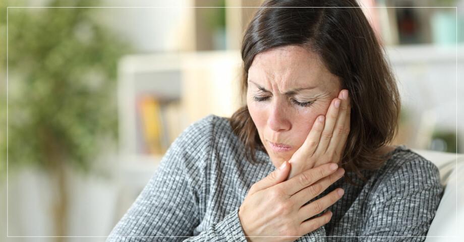 Kvinna trycker handen mot smärtande kind