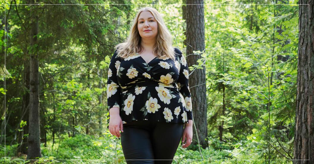 Ung blond kvinna i grönskande skog