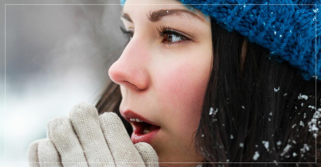 kvinna i kyla värmer händerna