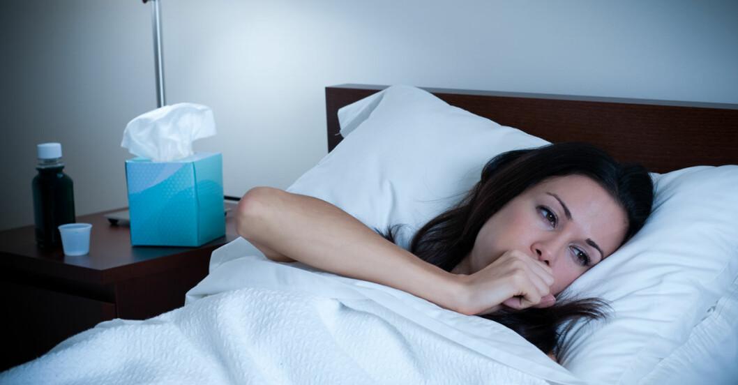 Kvinna ligger i sängen och hostar på natten