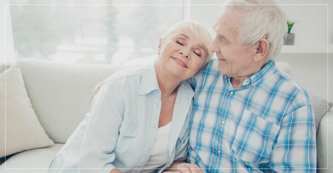 lyckligt åldrande par kramas i soffan