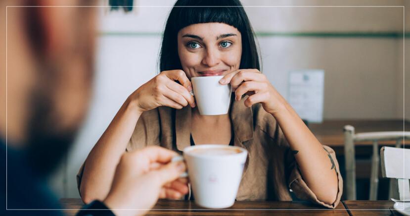 Kvinna ler och dricker kaffe