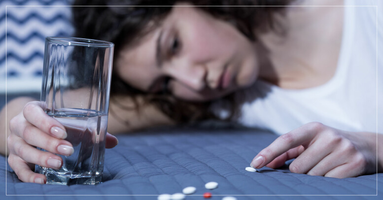 Deprimerad kvinna ligger i sängen med en hög piller