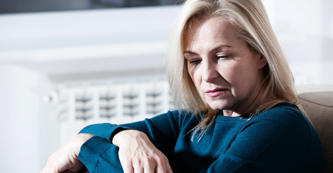 Kvinna som lider av depression sitter i sin säng
