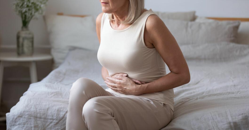 Kvinna sitter på säng och håller sig för magen