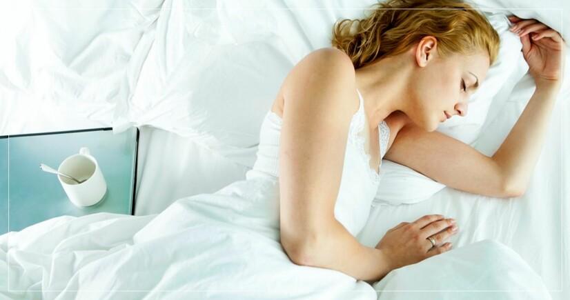 kvinna sover med duntäcke