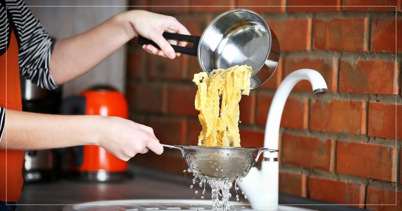 Person häller pasta från kastrull till durkslag