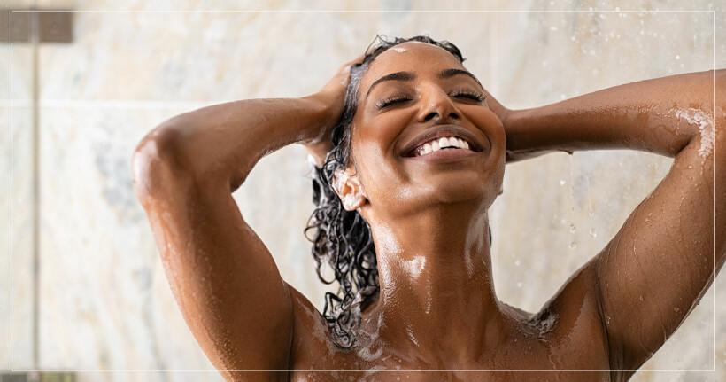 Kvinna ler samtidigt som hon tvättar håret