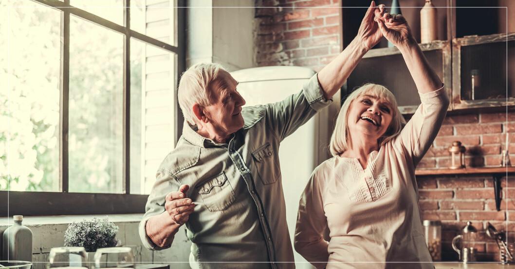 En äldre man och kvinna dansar tillsammans i köket