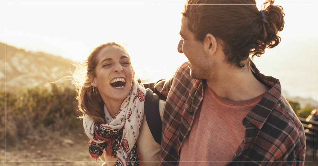 En kvinna och en man skrattar och håller om varandra i naturen.