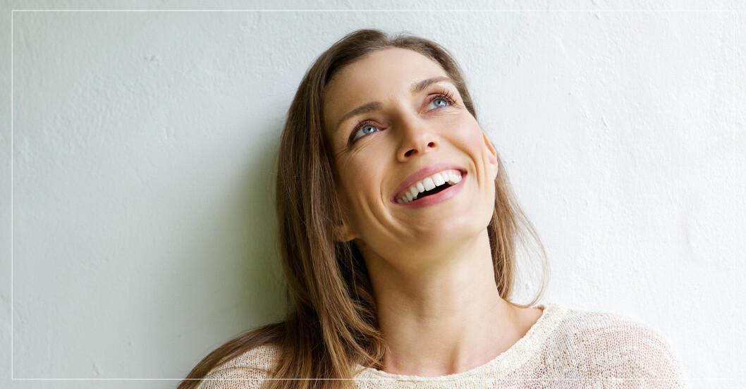 En leende kvinna står framför en vit vägg och tittar upp mot taket.