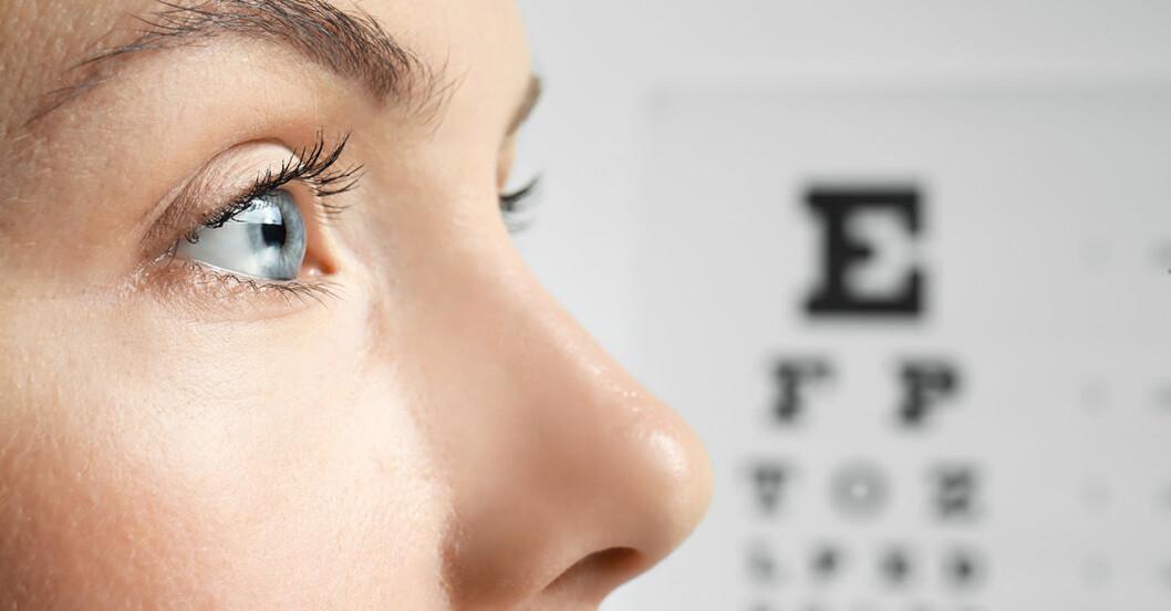 Kvinna med öppet öga, en optikertavla med bokstäver i bakgrunden