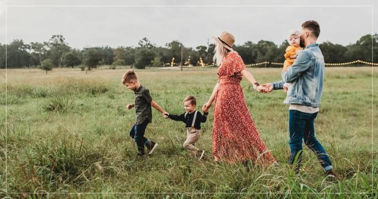 familj håller i hand och går i gräset