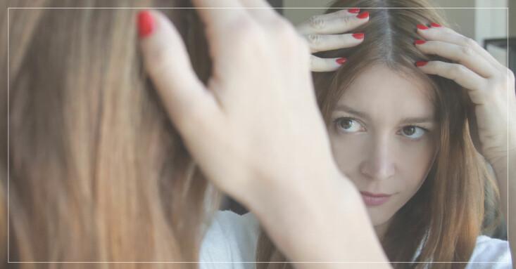 kvinna funderar över färg hon ska välja för att täcka sina grå hår