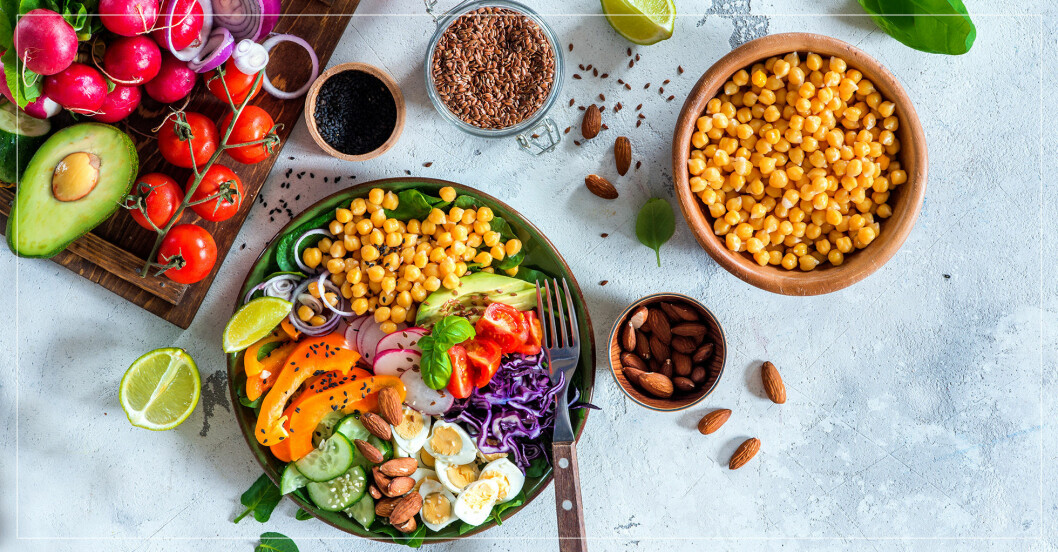 Massor av olika livsmedel och en tallrik med kikärtor, ägg, nötter och grönsaker.