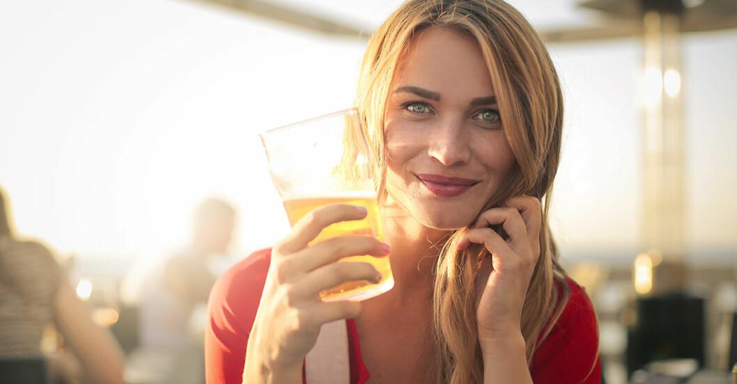 Ung tjej på uteservering med ett halvfullt glas i handen