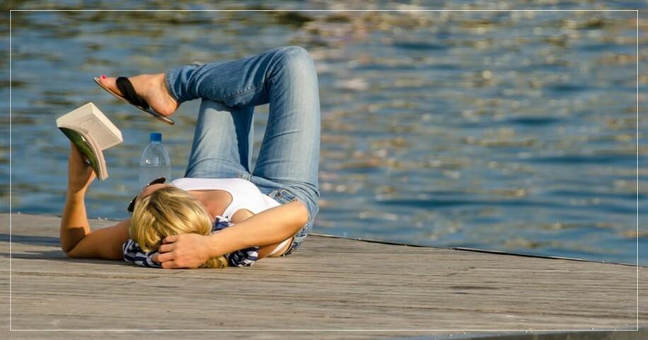 Kvinna slappar på en brygga med en bok
