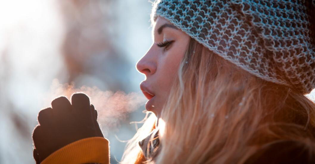 Kvinna som fryser på vintern och blåser varmluft på sina fingrar.