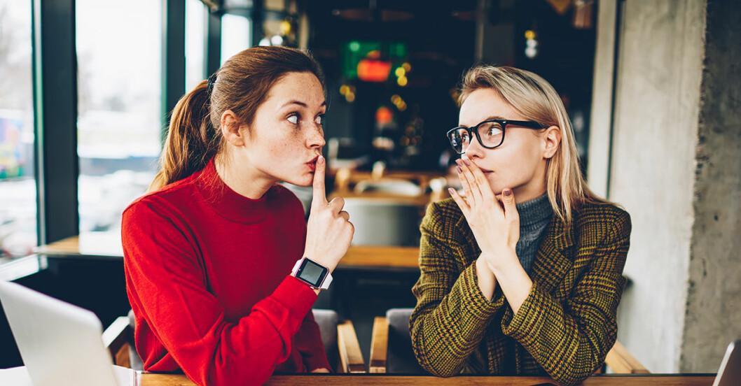 Två kvinnor skvallrar vid ett bord