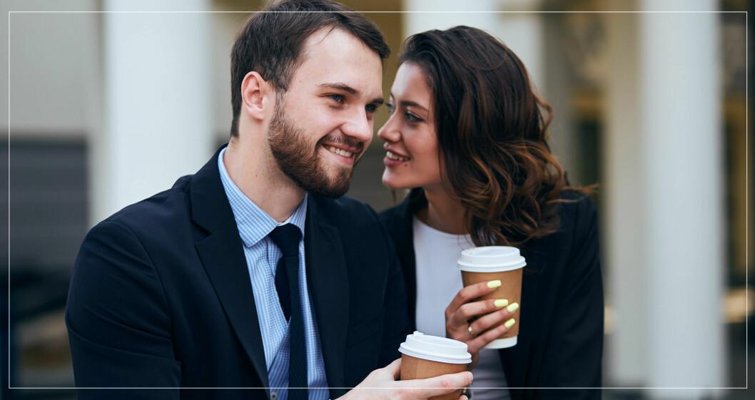 Kvinna viskar flörtande till man med kaffemugg.