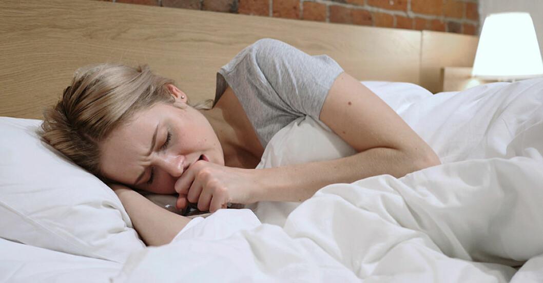 Blond kvinna med rynkad panna ligger i säng med vita sängkläder och håller knuten näve framför öppen mun.