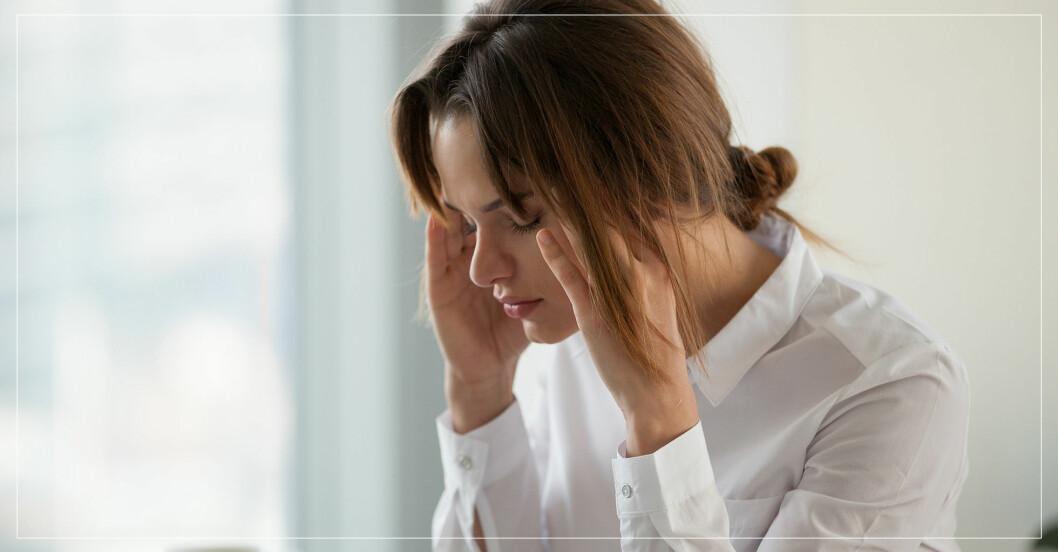 En trött kvinna som håller sig för huvudet.