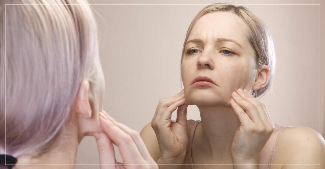 Kvinna tittar bekymrat på sin hud i spegeln