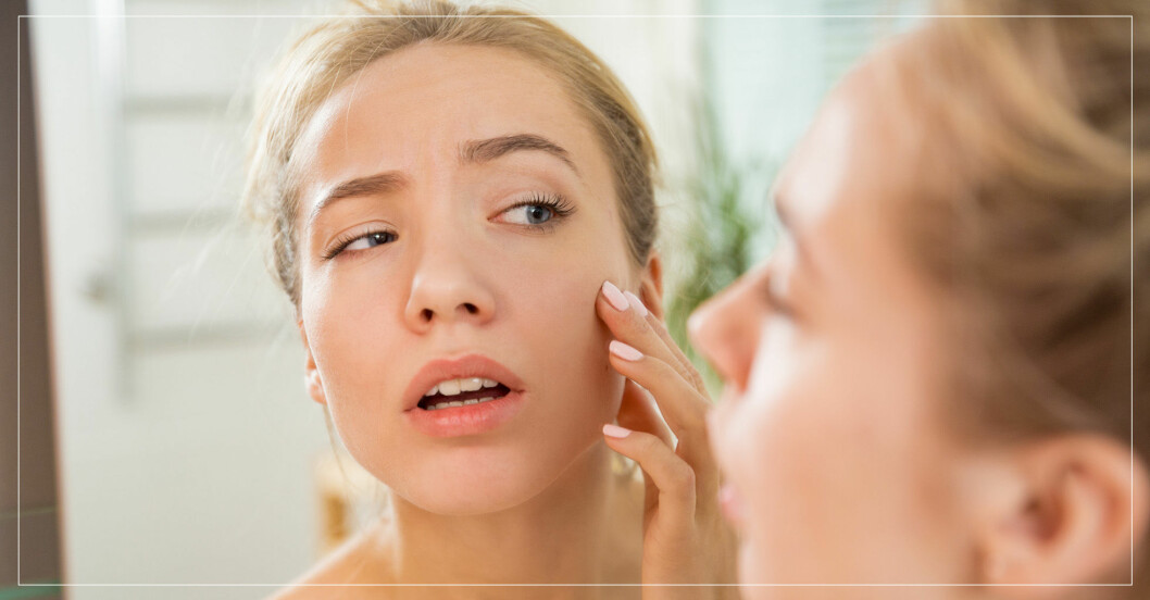 kvinna inspekterar sin hud i spegeln