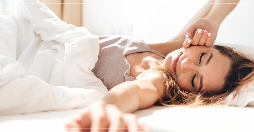 kvinna som ligger och sträcker på sig i sängen.