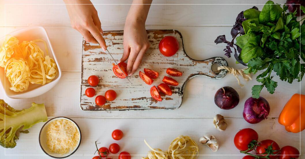 kvinna som skivar tomater på en skärbräda