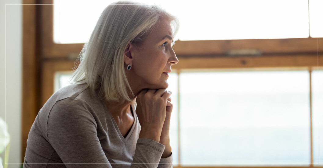 ledsen äldre kvinna som tittar ut genom fönster