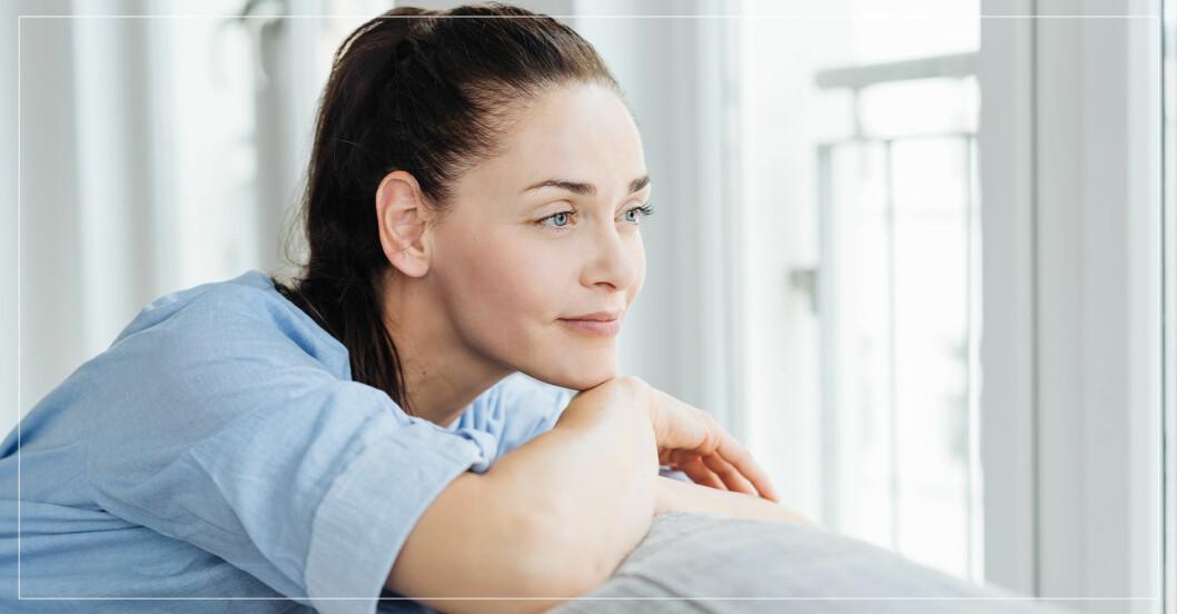Tankfull kvinna tittar ut genom fönster