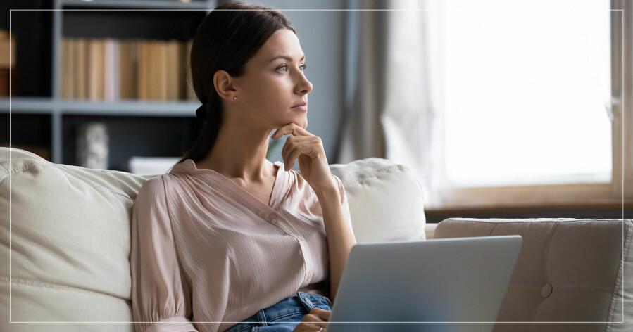 Kvinna sitter vid datorn och blickar ut